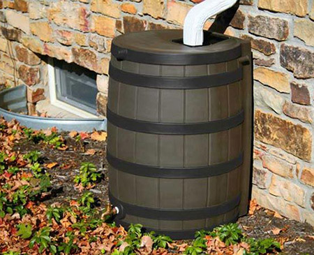 A residential rain barrel assembled and installed against the side of a home