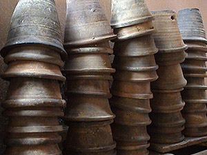 Picture of several clay pot containers stacked upside down.