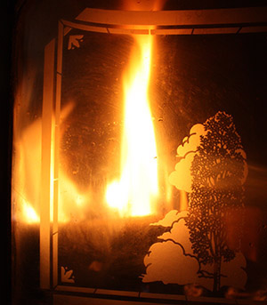 Photograph of fire in fireplace behind screen.