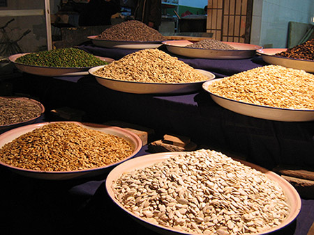 A variety of seeds organized in bowls and laid out in a market stand.