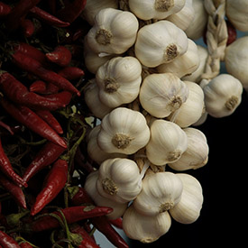 Picture of a strand of garlic and peppers.