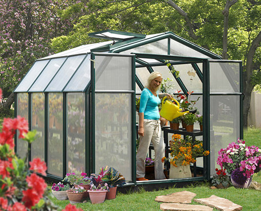 An assembled hobby greenhouse kit with a home owner tending to plant growing inside