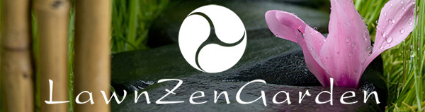 A flower sitting with a group of dark rocks, bamboo, grass and the LawnZenGarden logo.