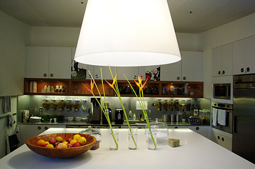 A picture of a modern, organized kitchen with a bowl of fruit on the white counter and a large white light overhead.